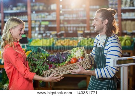 Male staff giving a crate of fresh vegetables to woman in organic section of supermarket