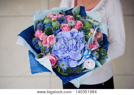 Big bouquet of white and blue flower in hands
