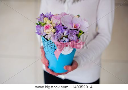 girl holding beautiful purple bouquet of mixed flowers in blue vase