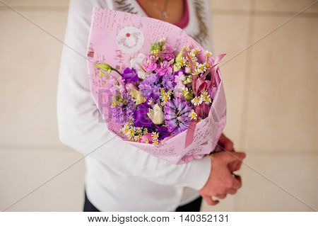 Bouquet with purple flower in girl hands