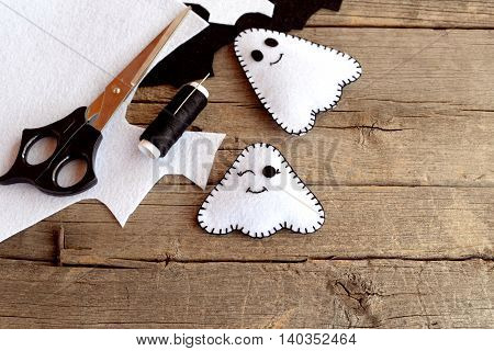 Halloween funny white ghosts diy, felt sheets, scissors, thread, needles on an old wood background. Easy Halloween felt bringing ornament. Sewing crafts idea for children