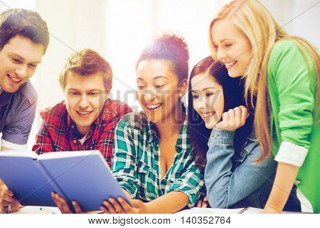 education concept - group of students reading book at school