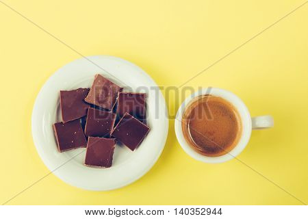 Chocolate on a saucer and a cup of coffee on a yellow surface top view