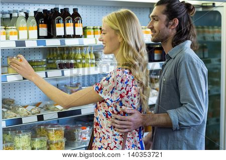 Happy couple shopping for groceries in supermarket