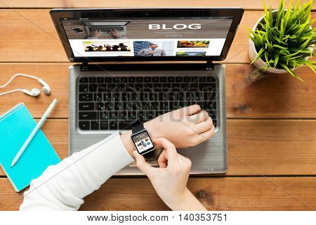 media, internet, business, people and technology concept - close up of woman with smart watch and laptop computer with blog web page on screen on wooden table