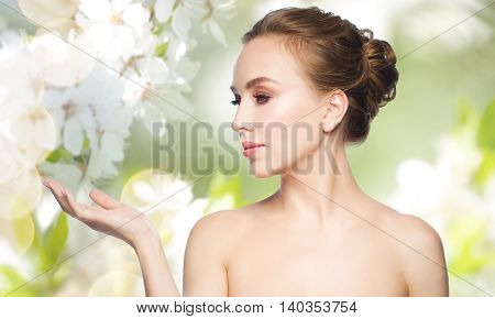 beauty, people, advertisement and health concept - smiling young woman holding something on palm of her hand over natural spring cherry blossom background