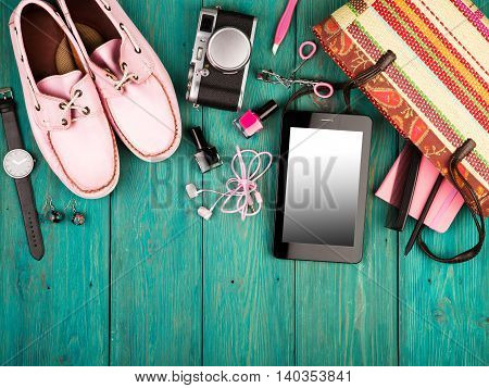 Shoes, Tablet Pc, Camera, Bag, Notepad, Watch, Headphones And Essentials On Blue Wooden Desk