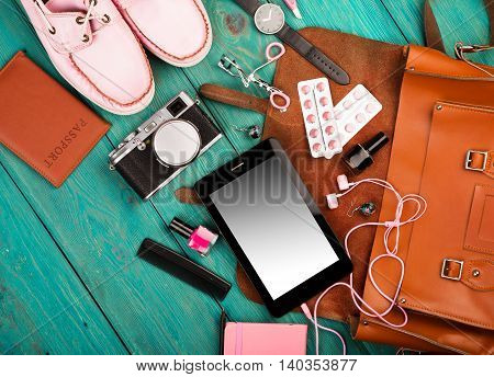 Shoes, Tablet Pc, Camera, Bag, Notepad, Headphones, Watch, Pills, Passport And Essentials On Blue Wo