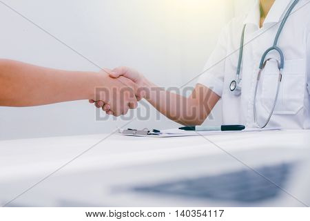 Doctor At The Clinic Giving An Handshake To His Patient, Healthcare And Professionalism Concept,doct
