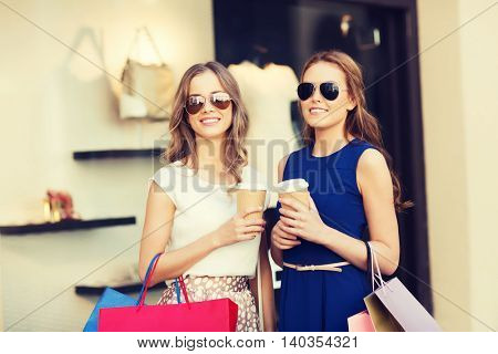 sale, consumerism and people concept - happy young women with shopping bags and coffee paper cups at shop window in city
