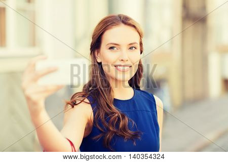 technology and people concept - happy young woman with smartphone taking selfie on city street