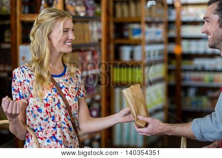 Smiling woman purchasing groceries in supermarket