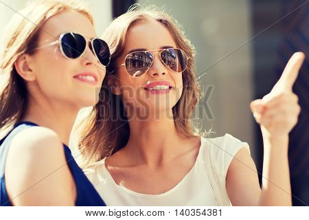 summer, fashion, accessories and people concept - happy women in sunglasses pointing finger in city