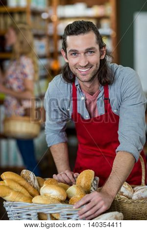 Portrait of male standing at bakery counter in supermarket