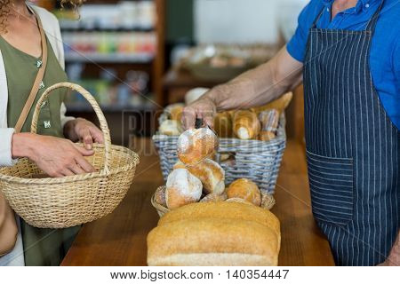 Mid section of woman purchasing bread at bakery store in supermarket