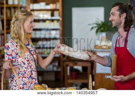 Smiling male staff giving loaf of bread to woman in supermarket