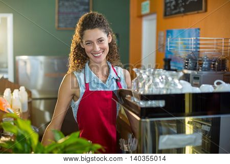 Portrait of smiling female staff standing at coffee shop counter in supermarket