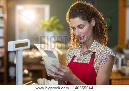 Female staff looking at a grocery item at payment counter in supermarket