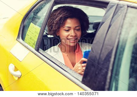 business trip, transportation, travel, gesture and people concept - young smiling african american woman texing on smartphone in taxi at city street
