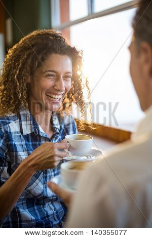 Smiling couple interacting with each other in super market while having tea