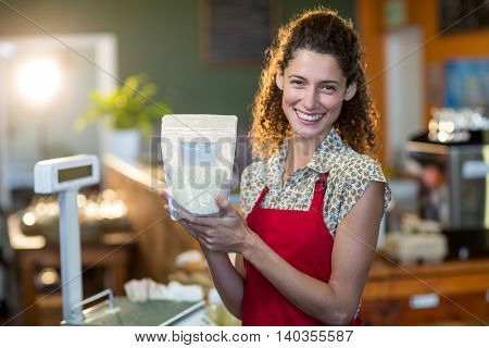 Smiling female staff holding a grocery item at payment counter in supermarket