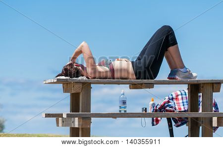 Mount Maunganui, New Zealand - November 8, 2012 Resting a young woman lies in warming sun on outdoor table recovering following the effort of walk to top of hill Drink bottle camera and shirt wait for her resumption of activity.