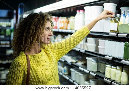 Woman buying a bottle of oil in supermarket
