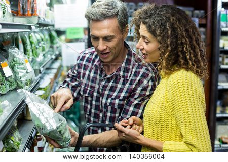 Happy couple selecting vegetables in supermarket