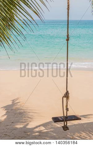 Swings on the sand tropical beach background.