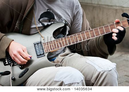 street musician playing on electric guitar