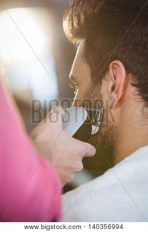 Man getting his beard trimmed at the hair salon