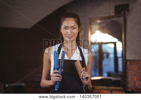 Portrait of female hairdresser holding straightener machine and comb at a salon