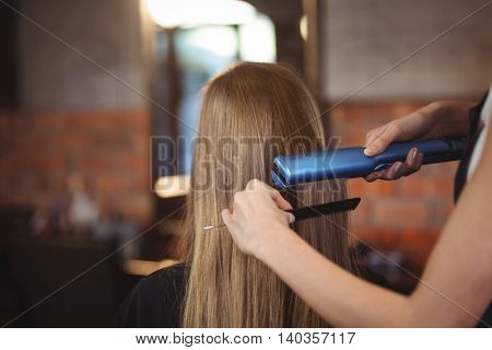 Female hairdresser straightening the hair of a client at a salon