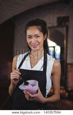 Portrait of female hairdresser holding bowl of hair dye at a salon