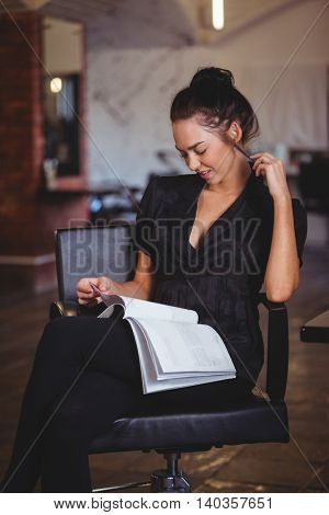 Smiling woman reading a magazine at the hair salon