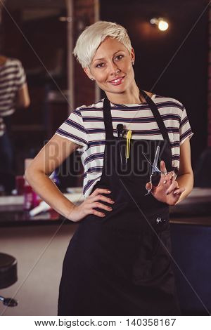 Portrait of female hairdresser standing with hand on hip at a salon
