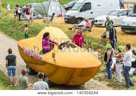 QuievyFrance - July 07 2015: St. Michel Madeleines vehicle during the passing of the Publicity Caravan on a cobblestoned road in the stage 4 of Le Tour de France on July 7 2015 in Quievy France.