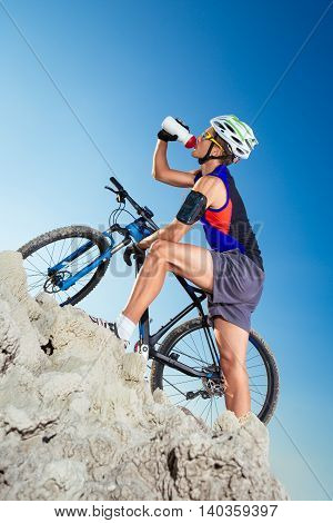 Cyclist drinks water on top of a mountain