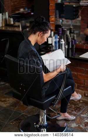 Woman reading a magazine at the hair salon