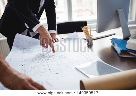 Midsection of male interior designer discussing blueprint with male coworker in office