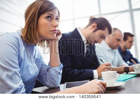 Thoughtful businesswoman with colleagues in meeting room at creative office