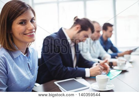Portrait of smiling businesswoman with coworkers in meeting room at creative office