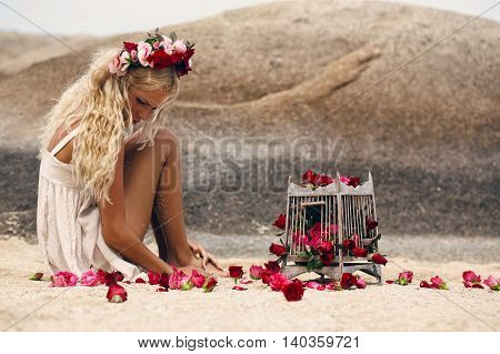 Retro vintage style image of beautiful blonde woman with roses and birdcage