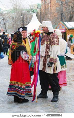 MOSCOW - MARCH 16, 2013: Woman and men in traditional costume. Shrovetide (Pancake week) celebration in Moscow city center.