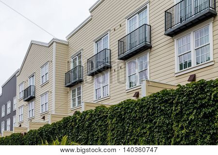 Yellow Siding Condos Over Hedge in Monterey