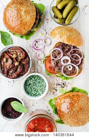 Homemade beef burgers with onion, pickles, fresh vegetables, spices, sun-dried tomatoes and tomato sauce on serving wooden board over white painted background. Top view, vertical composition