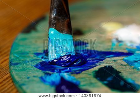 Close up photo of mixing oil paints on palette. Copy space.