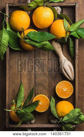 Fresh oranges with leaves in dark wooden tray over wooden background, top view, copy space, vertical composition