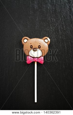 Funny chocolate bear over black stone table. Top view. Space for text