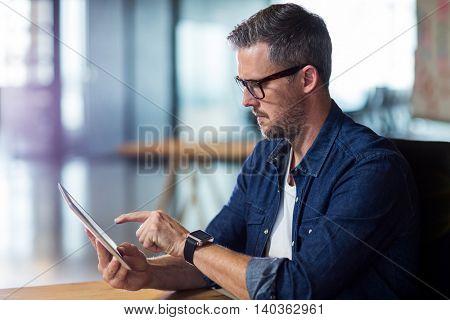 Focused man using digital tablet in office